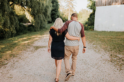 Romantic man and girlfriend strolling hand in hand on rural dirt track, rear view - p924m2039597 by Sara Monika