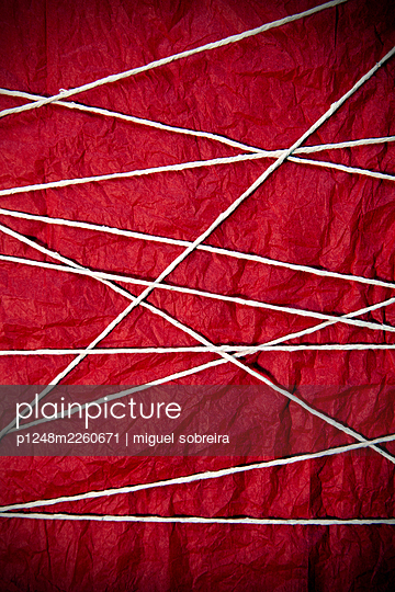Taut String across red fabric - p1248m2260671 by miguel sobreira