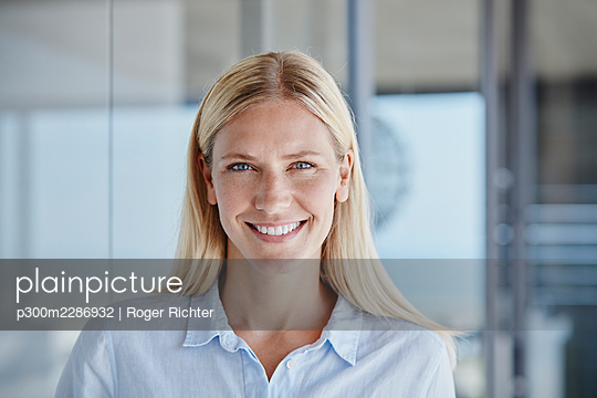 Smiling woman with blond hair at home - p300m2286932 by Roger Richter