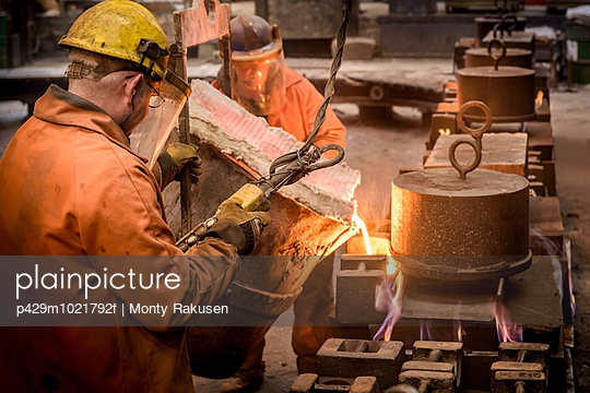 Workers pouring molten metal from flask in foundry - p429m1021792f by Monty Rakusen