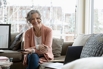 Portrait smiling, confident senior woman working from home, using smart phone and laptop on sofa - p1192m2088248 by Hero Images