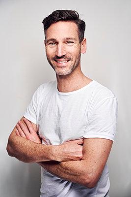 Portrait of man wearing white t-shirt - p300m2114833 by Philipp Nemenz