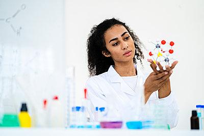 Young female researcher analyzing molecule model in laboratory - p300m2266241 by Giorgio Fochesato