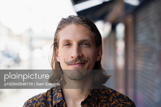 Portrait confident young male hipster with mustache - p1023m2046729 by Sam Edwards