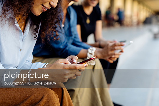 Three women sitting on steps in a row, using smartphones - p300m2155776 by Sofie Delauw