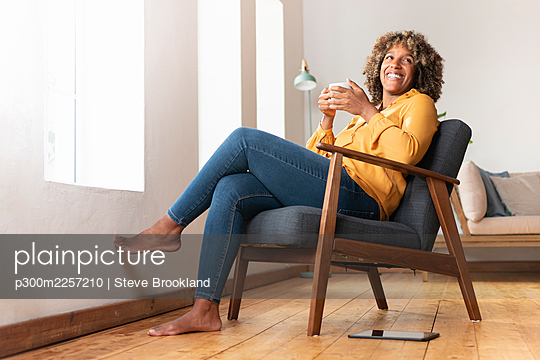 Smiling woman with tea cup looking away while sitting on armchair at home - p300m2257210 by Steve Brookland