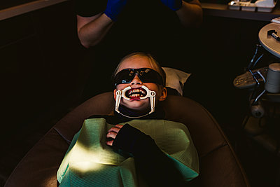 Young patient in dentist office having braces attached - p1166m2131116 by Cavan Images
