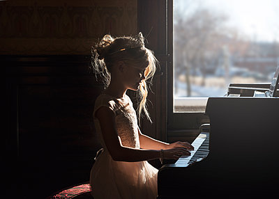 Lovely Young Girl at a Piano in a Shaft of Light - p1166m2157431 by Cavan Images