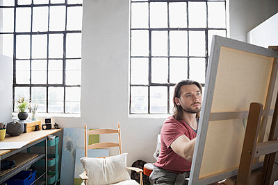 Male painter painting at canvas on easel in art studio - p1192m1490154 by Hero Images