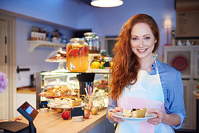 Portrait of smiling young woman serving cake in a cafe - p300m2023975 von gpointstudio