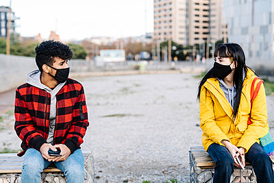 Couple wearing protective face mask sitting at social distance on bench during COVID-19 - p300m2242903 by COROIMAGE