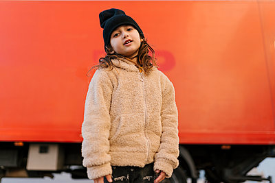 Cute girl wearing knit hat and sweater staring while standing against red truck - p300m2265333 by Ezequiel Giménez