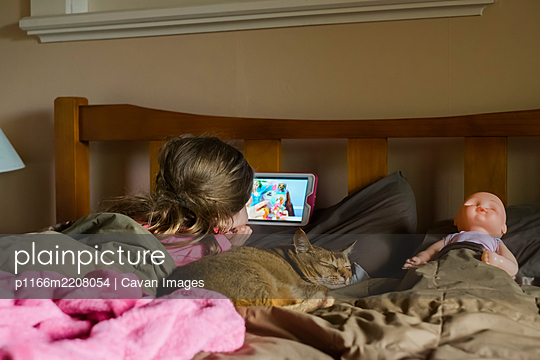 Young girl watching her device in bed with her cat and doll - p1166m2208054 by Cavan Images