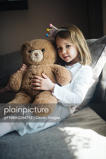 Happy little girl hugging a teddy bear at home. - p1166m2294712 by Cavan Images