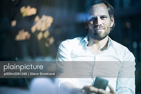 Smiling smart business man holding smartphone in modern office space looking out of window - p300m2081249 by Steve Brookland