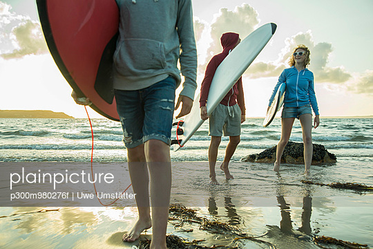 Three teenagers with surfboards walking at waterside of the sea - p300m980276f by Uwe Umstätter