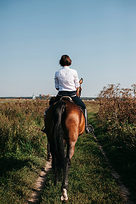 Rear view of female rider riding horse on grassy field against clear blue sky during sunny day - p1166m2024889 by Cavan Images