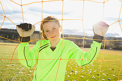 Portrait of confident goalie standing behind net - p1192m1043660f by Hero Images