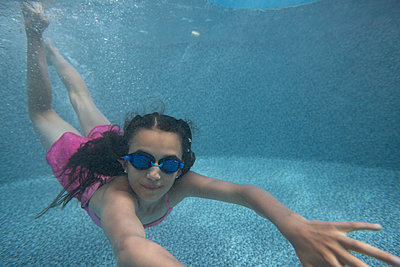 Portrait girl wearing goggles swimming underwater in swimming pool - p1192m1183977 by Hero Images