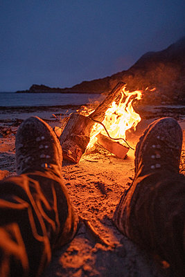 Wanderschuhe vor einem Lagerfeuer am Strand - p1455m2204400 von Ingmar Wein