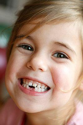 Girl showing her milk teeth - p2490470 by Ute Mans