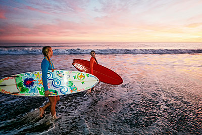 Women carrying surfboards in ocean waves at beach - p555m1305261 by Peathegee Inc