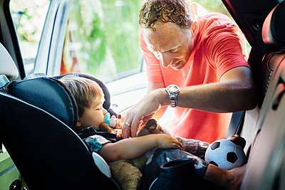 Father putting on seatbelt for son in car seat - p1166m1164243 by Cavan Images