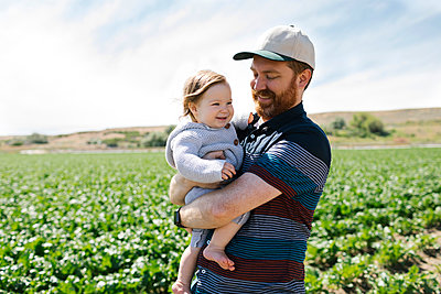 Smiling father holding baby girl in crop field - p1427m2128239 by Jessica Peterson