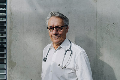 Portrait of a confident senior doctor at a concrete wall - p300m2155387 by Joseffson