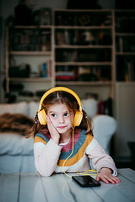 Girl wearing headphones looking away while leaning on table at home - p300m2225336 by Eva Blanco
