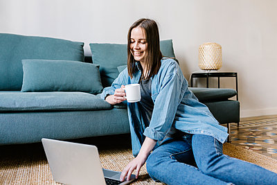 Smiling young woman using laptop while having coffee by sofa at home - p300m2282669 by Xavier Lorenzo