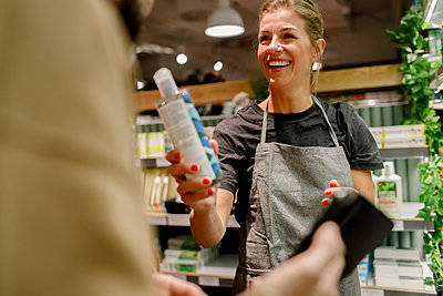 Smiling saleswoman assisting male customer in supermarket - p426m2218839 by Maskot