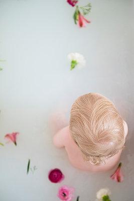 Caucasian baby boy in milk bath with flowers - p555m1491562 by JGI