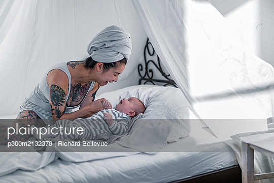 Tattooed young woman with her baby in canopy bed - p300m2132378 by Richárd Bellevue