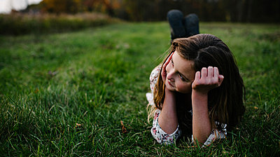 Thoughtful girl lying on grassy field at park - p1166m1555650 by Cavan Images