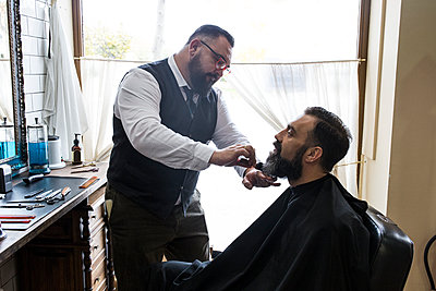 Barber brushing the beard of a man with a hair brush - p300m1206142 by Andrés Benitez