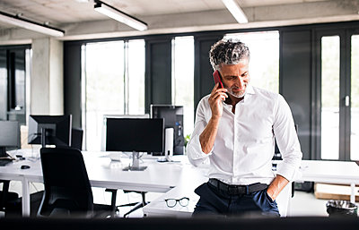 Mature businessman on cell phone in office - p300m1535283 by HalfPoint