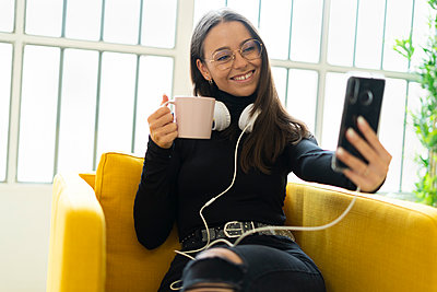 Smiling young female blogger taking selfie with coffee cup and headphones against window at home - p300m2225802 by Giorgio Fochesato