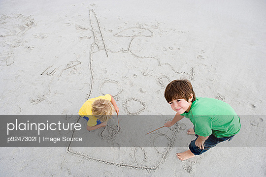 Boys drawing in sand - p9247302f by Image Source