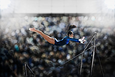 A female gymnast, a young woman performing on the parallel bars, in mid flight reaching towards the top bar.  - p1100m1095656 by Mint Images