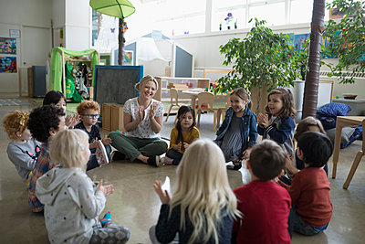 Preschool teacher and students clapping in circle on floor in classroom - p1192m1560188 by Hero Images