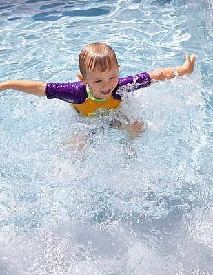 Little boy splashing about in swimming pool - p1640m2254809 by Holly & John