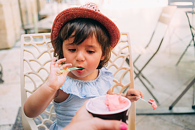 Cute toddler girl eating an ice cream held by her mother - p300m2012546 von Gemma Ferrando