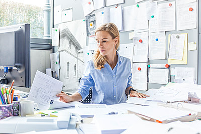 Woman sitting at desk in office doing paperwork - p300m2070866 by Tom Chance