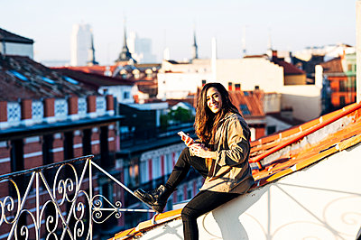 Happy young woman with mobile phone on rooftop during sunny day - p300m2243618 by Jose Luis CARRASCOSA