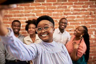 Smiling businesswoman taking selfie with colleagues in coworking office - p300m2283007 by Zeljko Dangubic