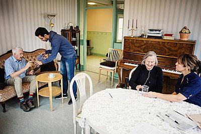 Caretakers taking care of senior people at nursing home - p426m1131113f by Maskot