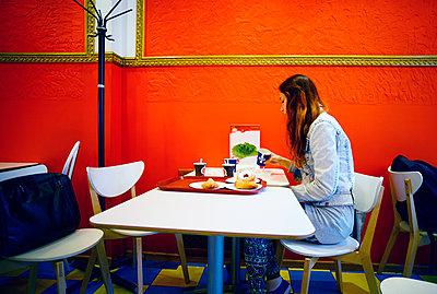 Caucasian woman eating in restaurant - p555m1311910 by Aleksander Rubtsov