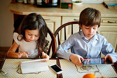 Caucasian brother and sister using digital tablets - p555m1411268 by Vladimir Serov