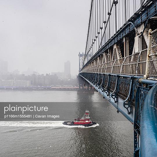 Manhattan Bridge over East River against sky during foggy weather - p1166m1555481 by Cavan Images